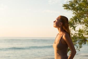 Frau beobachtet Sonnenuntergang