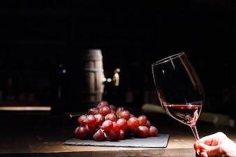 Frau hält Glas Wein vor Haufen Traube auf schwarzem Teller liegen