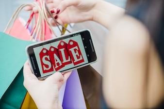Frau hält Smartphone mit Inschrift auf dem Bildschirm