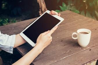 Frau Hand halten Tablette und leere Bildschirm-Display auf Holztisch in Café-Shop.