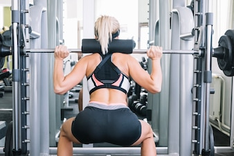 Frau hebt Bar im Fitness-Studio