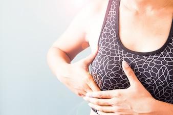 Frau im Sport BH mit ihrer Brust, Brustkrebs Anhebung Bewusstsein konzeptionelle Idee / Gesundheitskampagne: Medizin, Versicherung, Organ Spende Konzept.