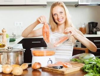 Frau kocht Gemüse und Lachs mit Elektrodampfer
