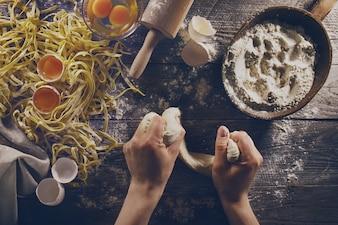 Frau kocht Hände vorbereiten leckere hausgemachte klassische italienische Pasta auf Holztisch. Nahansicht. Draufsicht. Toning