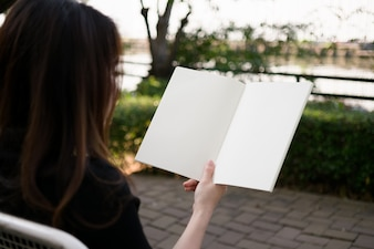 Frau liest leeres Buch im Garten
