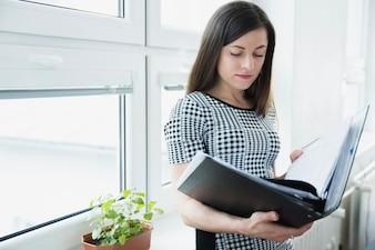 Frau mit großen Ordner posiert im Büro