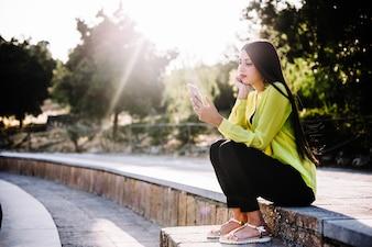 Frau mit Handy im sonnigen Park