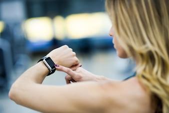 Frau mit smart Uhr in der Turnhalle