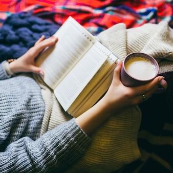 Frau mit Tasse Kaffee und Buch liegt unter bunten Plaids