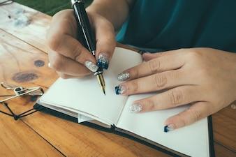 Frau sitzt am Tisch und schreibt im Notizbuch in schönem Licht Heimat Innenraum. Zuhause arbeiten. Freiberufler. Ideen schreiben. drinnen. Vintage gefiltertes Bild.