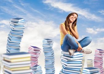 Frau sitzt auf Bücher