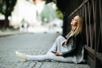 Frau sitzt und träumt auf Pflaster