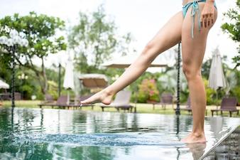 Frau steht am Poolrand und berührt Wasser