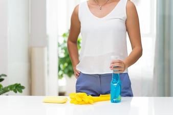 Frau steht in der Nähe Tisch mit Reinigungsmitteln