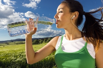 Frau trinkt Wasser nach sportlichen Aktivitäten