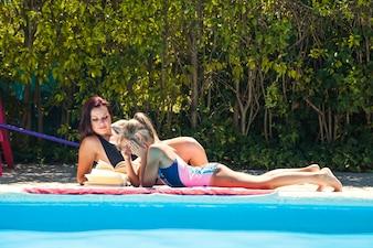 Frauen liest Buch liegend am Pool