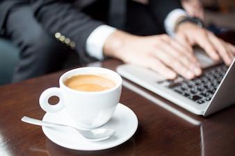 Freigestellte Ansicht des Mannes, der an Laptop im Kaffee arbeitet