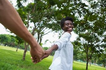 Freudige junge Frau führt ihren Mann von Hand im Park