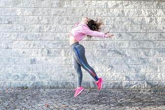 Freudige sportliche Frau, die auf Straße springt