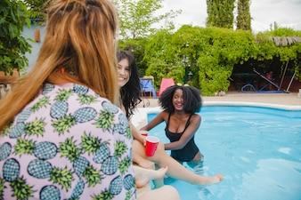 Freunde scherzen am Schwimmbad