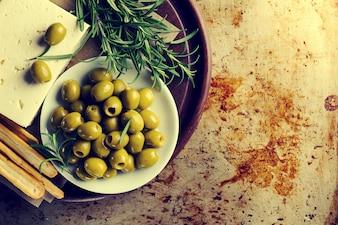 Frische, leckere griechische grüne Oliven mit Käsefeta oder Ziegenkäse. Nahansicht. Mediterranes Essen.Toning.