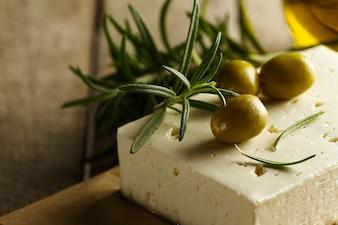 Frische, leckere griechische grüne Oliven mit Käsefeta oder Ziegenkäse. Nahansicht. Mediterranes Essen.