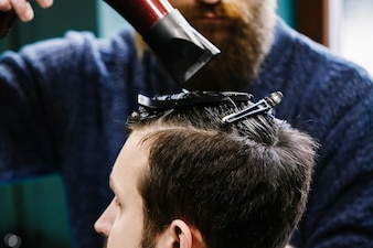 Friseur benutzt einen Fön, während er die Haare des Mannes schneidet