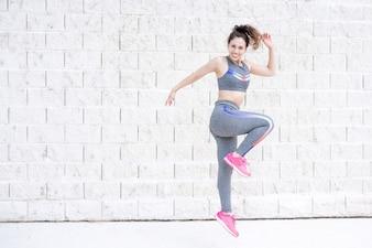 Frohe sportliche Frau, die nahe Wand springt