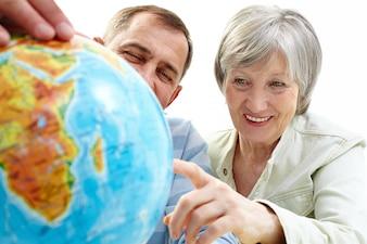 Fröhlich Paar zeigt auf Globus