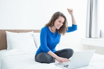 Fröhliche Dame arbeitet am Laptop und sitzt auf dem Bett