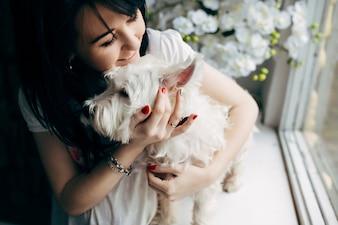 Fröhliche Frau, die mit Hund kuschelt