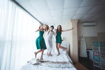 Fröhliche Frauen, die vor der Hochzeit auf dem Bett springen