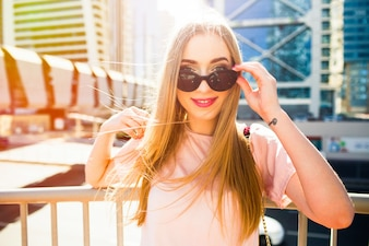 Fröhliche junge Frau schaut über ihre Sonnenbrille posiert unter dem