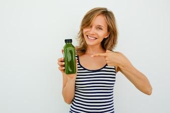 Fröhliche junge Frau zeigt auf grüne Flasche