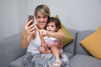 Fröhliche Mutter, die Selbstmutter mit Tochter nimmt