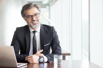 Fröhlicher Geschäftsmann in Brillen im Büro