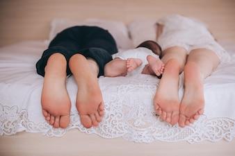 Fuß Väter Mama und Baby im Bett