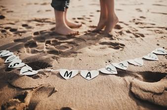Füße eines pare in den Sand des Strandes mit einer Nachricht
