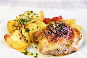 Gebratenes Hähnchen mit Kartoffeln und Gemüse.