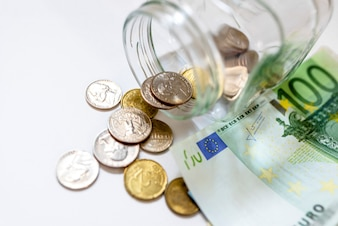 Geld in Glas Glas auf weißem Hintergrund