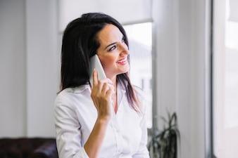 Geschäftsfrau, die auf Smartphone spricht