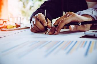 Geschäftsfrau, die Investitionsdiagramme zur Morgenzeit analysiert.