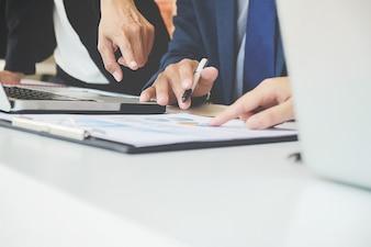 Geschäftskonzept. Geschäftsleute diskutieren die Diagramme und Grafiken, die die Ergebnisse ihrer erfolgreichen Teamarbeit zeigen.