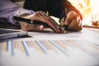Geschäftsleute, die Investitionsdiagramme zur Morgenzeit analysieren.
