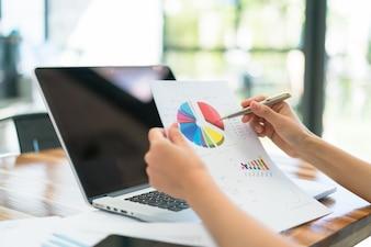 Geschäftsleute mit Laptop und finanzielle Charts auf Sitzung Büro