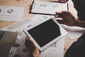 Geschäftsmann arbeitet mit leeren Bildschirm digitale Tablette und Laptop auf hölzernen Schreibtisch im Büro.