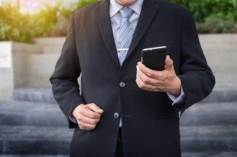 Geschäftsmann mit schwarzen Anzug und mit modernen Smartphone im Freien