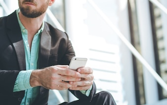 Geschäftsmann mit Smartphone im Freien des Bürogebäudes