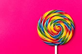 Geschmackvolle appetitliche Party Zubehör Sweet Swirl Süßigkeiten Lollypop auf rosa Hintergrund Draufsicht