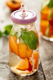 Gesunde leckere frische erfrischende Entgiftung Wasser in Flaschen oder Gläser mit Aprikosen, Minze und Eis auf Holzuntergrund. Nahansicht. Gesundes Lebenskonzept.